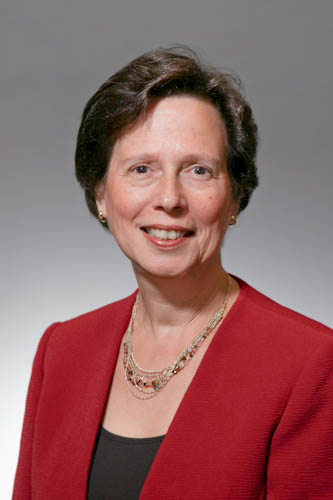 Professor Beizer's professional head shot, wearing a red blazer and black top