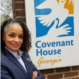 "Alieizoria ""Alie"" Redd standing next to Covenant House sign"