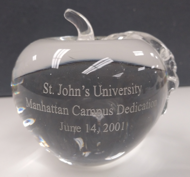Clear glass apple shaped paper weight engraved with St. John's University Manhattan Campus Dedication Ceremony, June 14, 2001.