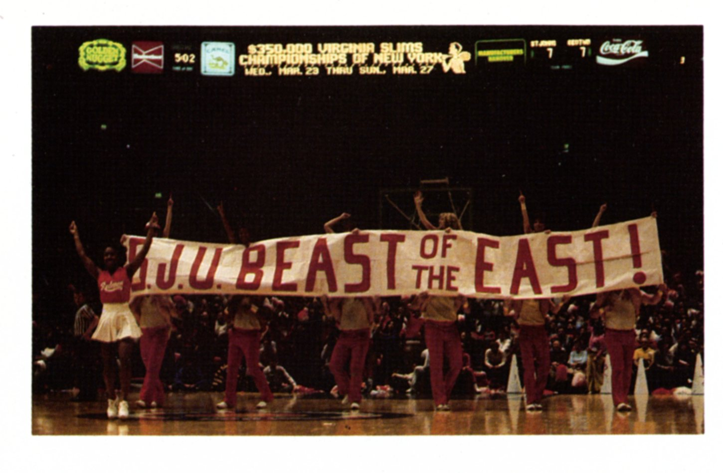 "Cheerleaders holding up a sign at a basketball game encouraging the audience to chant ""Beast of the East"" in 1983."