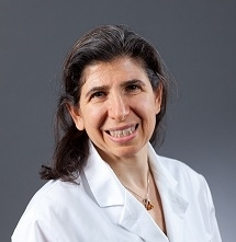Professional head shot of Professor Sandra E. Reznik wearing a white top.  Image has a gray background.