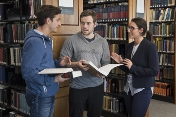 Three law students conversing in the library