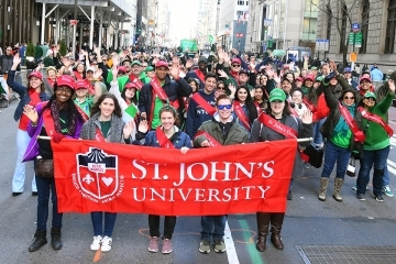 Students and Alumni holding St. John's Banner at St. Patrick's Day Parade