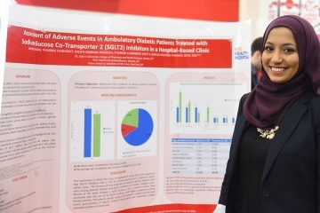 Female student standing infront of research poster