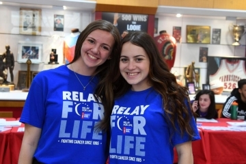 Two students posing with Relay for Life t-shirts on