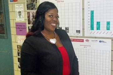 Latasha Jones stands in front of graphs
