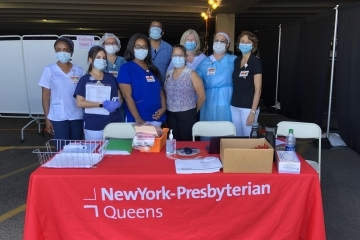 Healthcare workers standing at table with NYP logo ready to check students temperatures as they return to campus