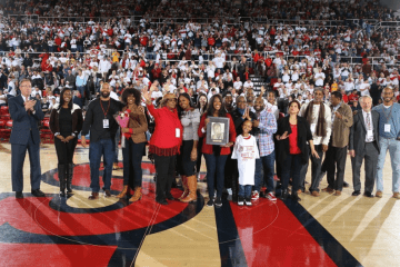 Solly Walker's family holding photo of him on the floor of Carnesecca Arena