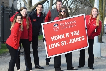 "Six students holding a ""Honk if you Love St. John's"" sign"