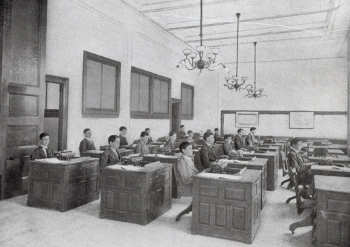 Students sitting at desks in the 1900s using typewriters