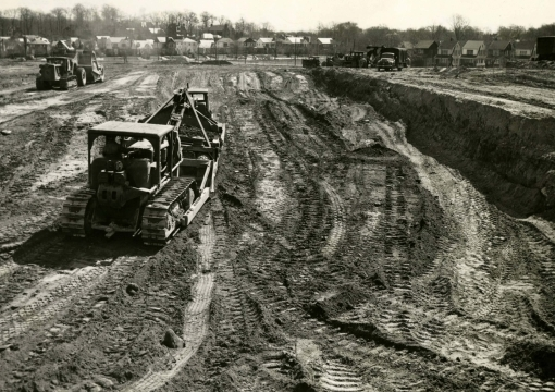Construction trucks clearing land in 1954