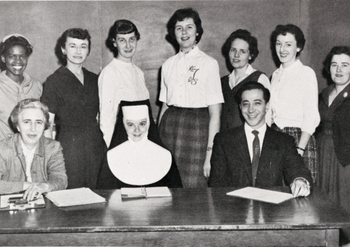 College of nursing students standing infront of desk for photo.