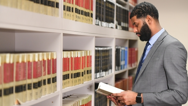 Male student in law library reading book