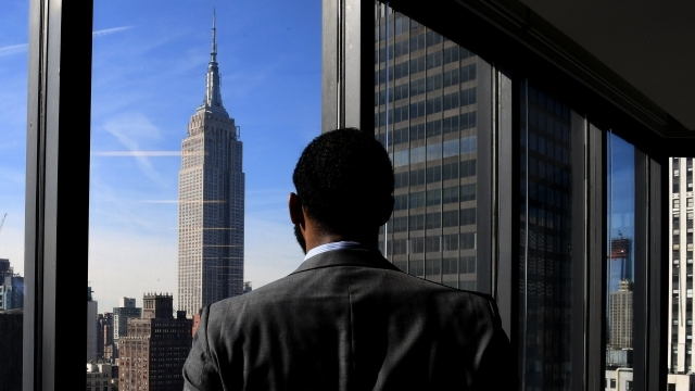 Male Student Looking Out City Window at Empire State Building