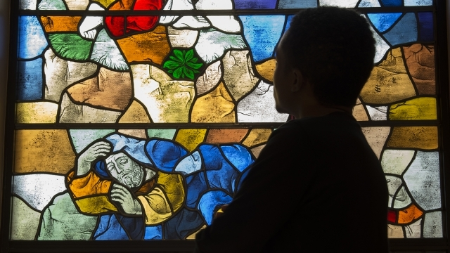 Student standing infront of stained glass window