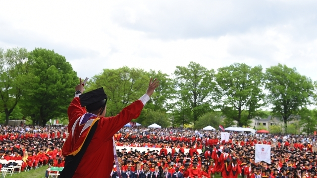 Male student holding is hands up as he walks across commencement stage