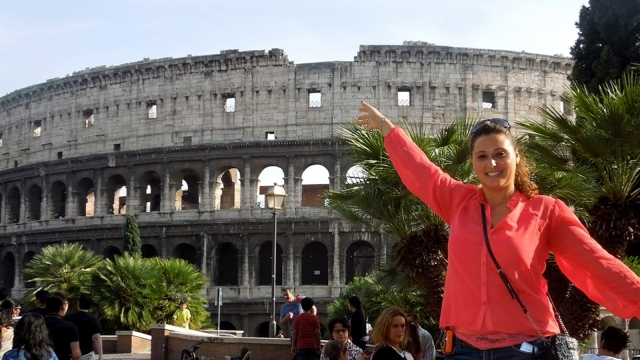 Female student posing infront of coliseum in Rome