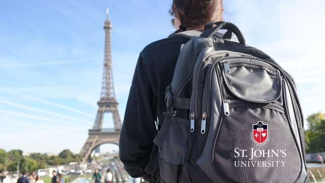 Student wearing St. John's University backpack infront of Eiffel tower