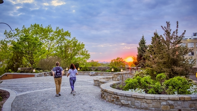 Students walking on campus at sunset