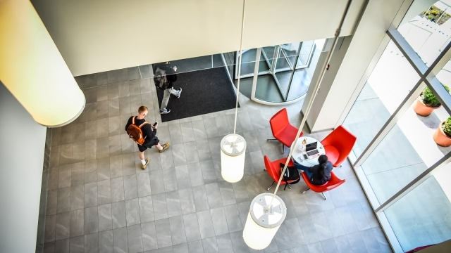 Student sitting at chairs and student walking through lobby of building