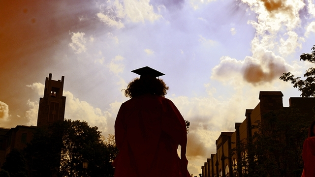 Female student walking away in cap and gown