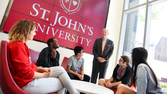 Faculty talking to students in front of St. John's logo
