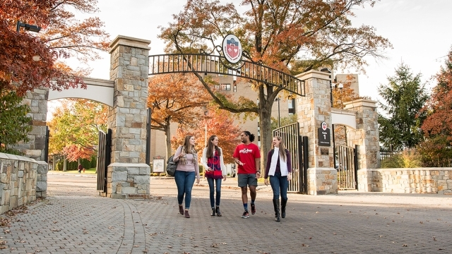 Four students walking out of the St. John's University front gate