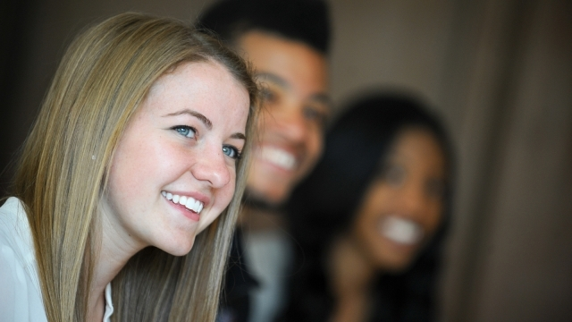 three students smiling at camera