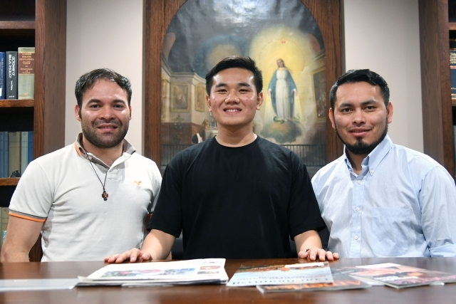 Three men standing infront of table with magazines