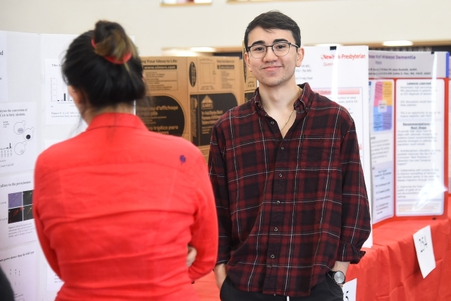 Male smiling at camera infront of research poster