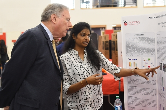 Female student pointing to poster board show Dean DiGate research