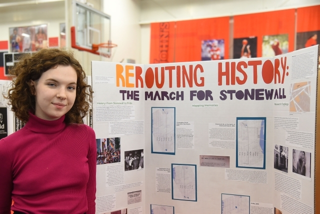 Female student standing infront of her research poster