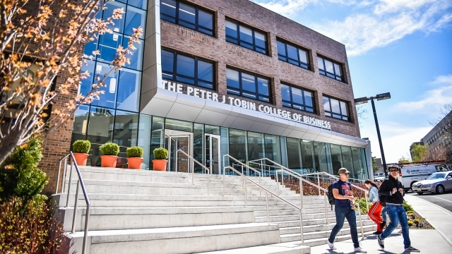 Exterior shot of Peter J. Tobin College of Business with students walking down the stairs