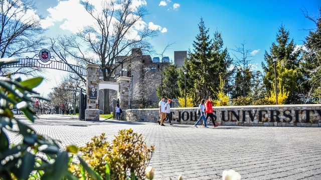 St. John's University front gate with students walking on/off campus