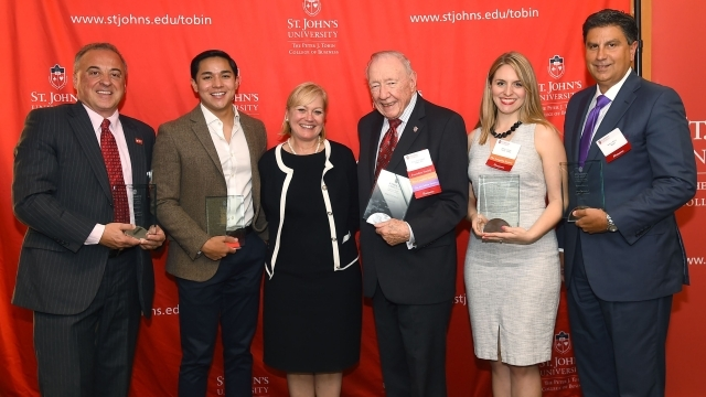 5 recipients of Tobin Alumni awards with Dean Sharpe in front of step and repeat