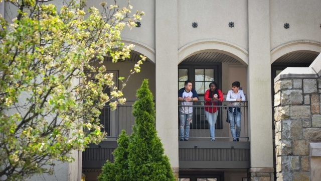 Three students talking to one another on the balcony