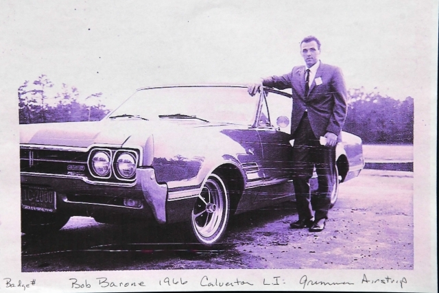 Bob Barrone standing infront of car in black and white photo