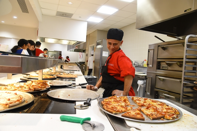 Dining hall worker making pizza