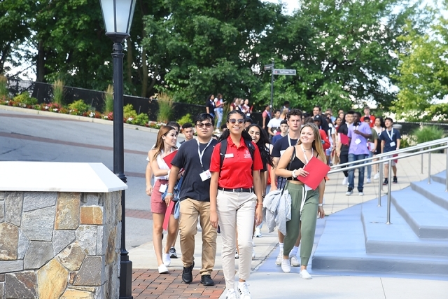 Students and orientation leader walking on campus