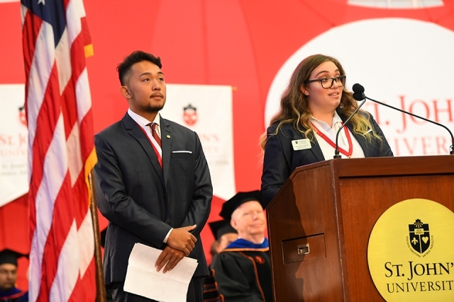 Two students speaking at podium with American flag next to them