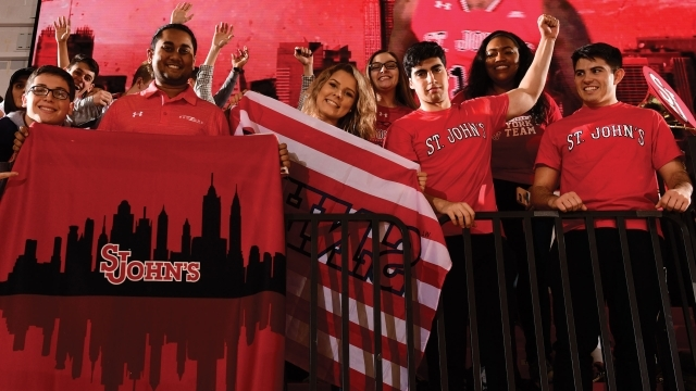 Fans cheering at basketball game holding St. John's flags