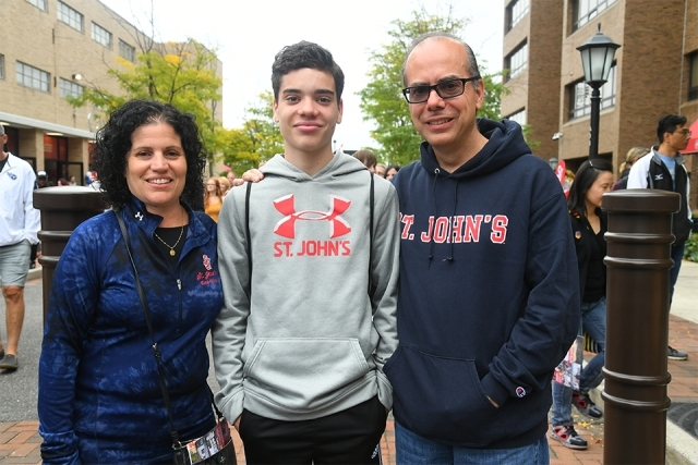 A family smiels for the camera in SJU clothing