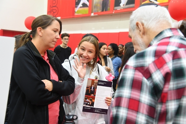 Guest waves at camera from Academic Fair