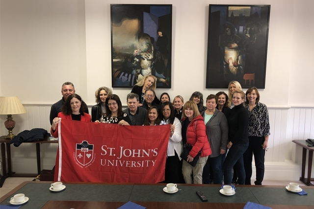Alumni and friends holding up a St. John's banner