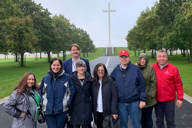 Alumni and Friends pose for a picture in front of an outdoor cross