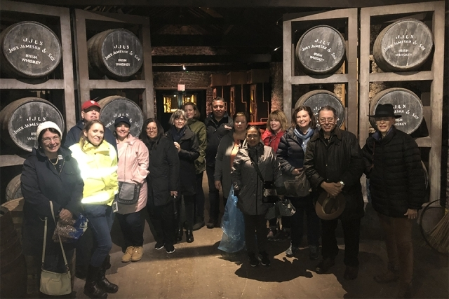 Alumni and Friends in Ireland in front of Jameson barrels