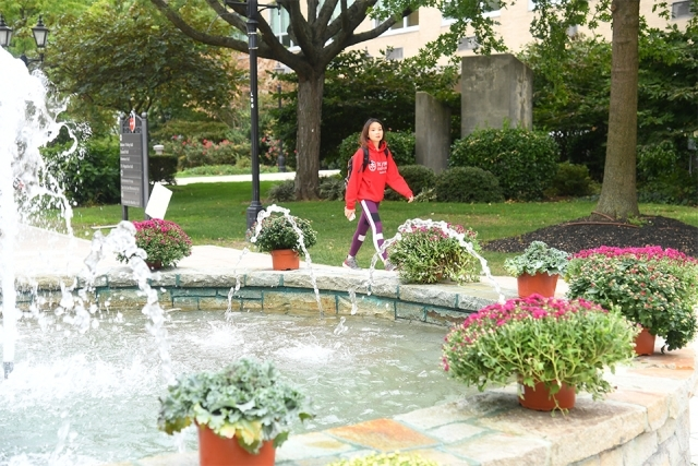 Student in SJU sweatshirt walks past fountain
