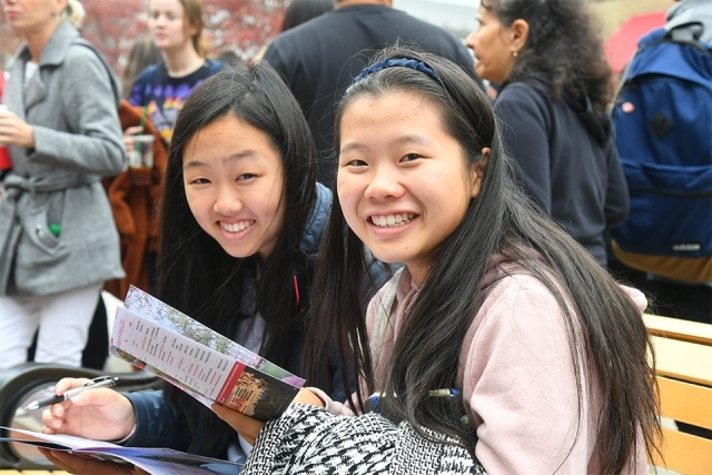 Students smile while looking at event program