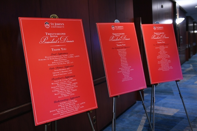Three red poster boards on easels displaying lists of President's Dinner supporters
