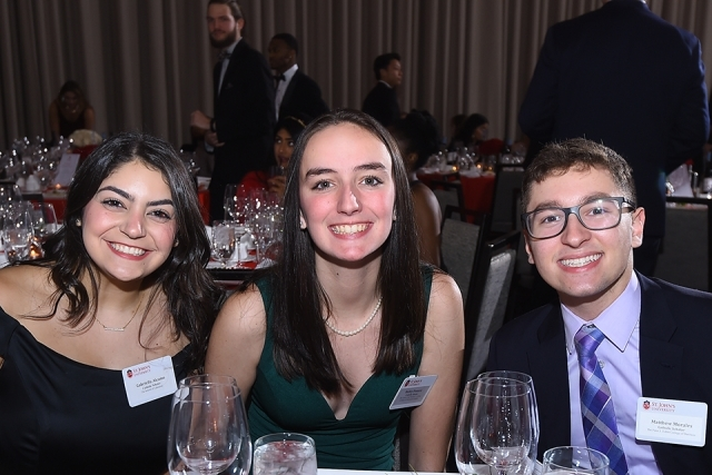 Three guests seated at a table pose for a photo at the St. John's University 2019 President's Dinner